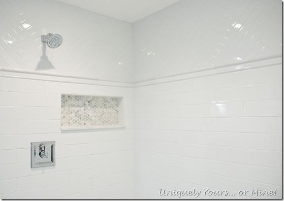 Master bathroom shower stall, white ceramic herringbone and subway with Carrera hexagon tile floors