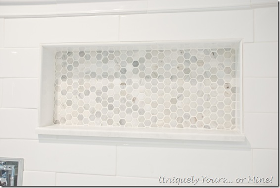 Master bathroom shower stall, white ceramic herringbone and subway with Carrera hexagon tile floors