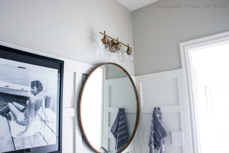 Board and batten DIY in guest bathroom, large round brass mirror and brass sconce